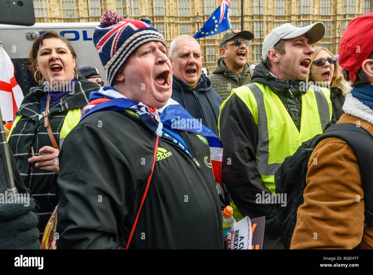 London, UK. 29th January 2019. Brexiteers shout together at EU Supergirl Madeleina Kay who is singing. On the day of more Brexit votes, protests around parliament continue, with Remainers waving EU flags, and Brexiteers holding signs leave means leave. A small group, some wearing yellow jackets came to shout at the Remainers, calling them traitors. Away from this there were a few more reasoned arguments, and others making their points with various costumes. Credit: Peter Marshall/Alamy Live News - Stock Image