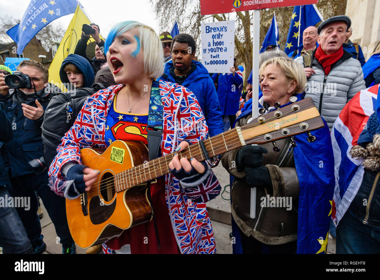London, UK. 29th January 2019. EU Supergirl Madeleina Kay sings despite the attempts of Brexiteers to shout and drown her voice. On the day of more Brexit votes, protests around parliament continue, with Remainers waving EU flags, and Brexiteers holding signs leave means leave. A small group, some wearing yellow jackets came to shout at the Remainers, calling them traitors. Away from this there were a few more reasoned arguments, and others making their points with various costumes. Movement for Justice on Parliament Square called Brexit racist. There was a large police presence. Peter Marshal - Stock Image