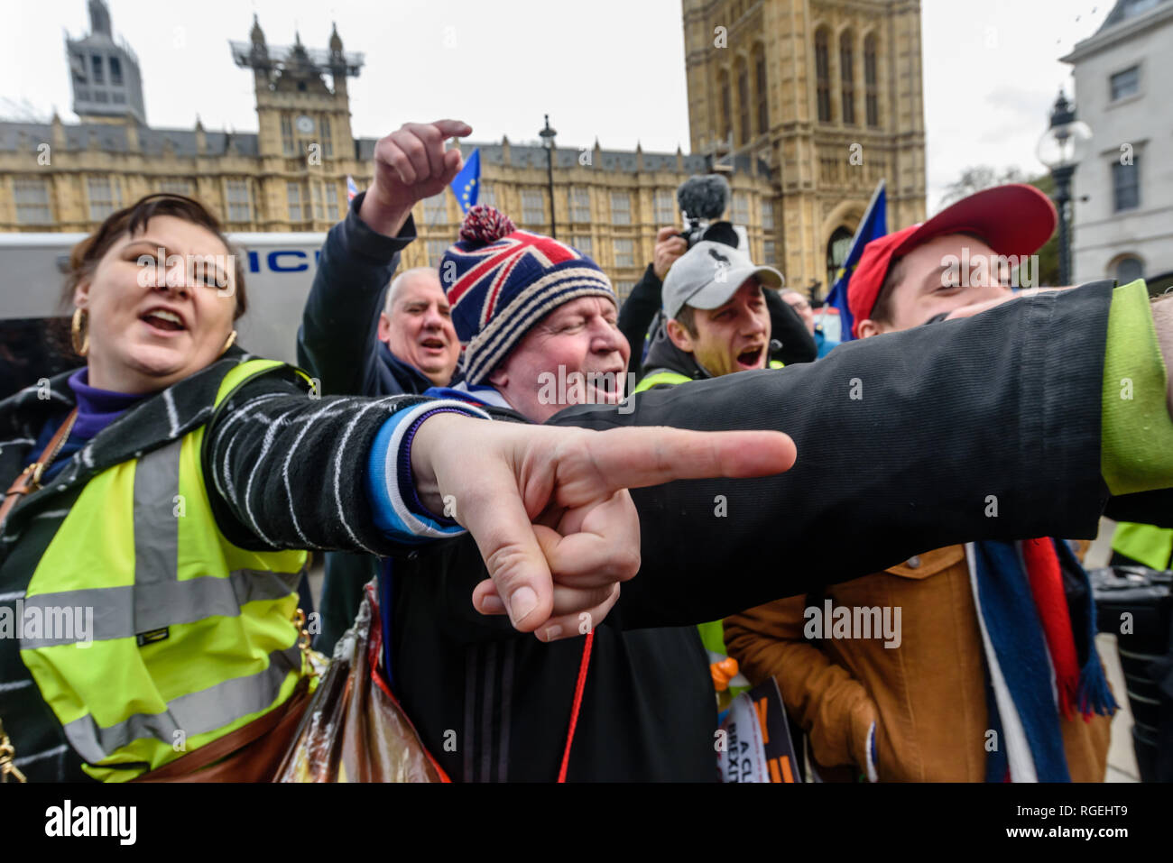 London, UK. 29th January 2019. Brexiteers point and shout at EU Supergirl Madeleina Kay who is singing.  On the day of more Brexit votes, protests around parliament continue, with Remainers waving EU flags, and Brexiteers holding signs leave means leave. A small group, some wearing yellow jackets came to shout at the Remainers, calling them traitors. Away from this there were a few more reasoned arguments, and others making their points with various costumes. Credit: Peter Marshall/Alamy Live News - Stock Image