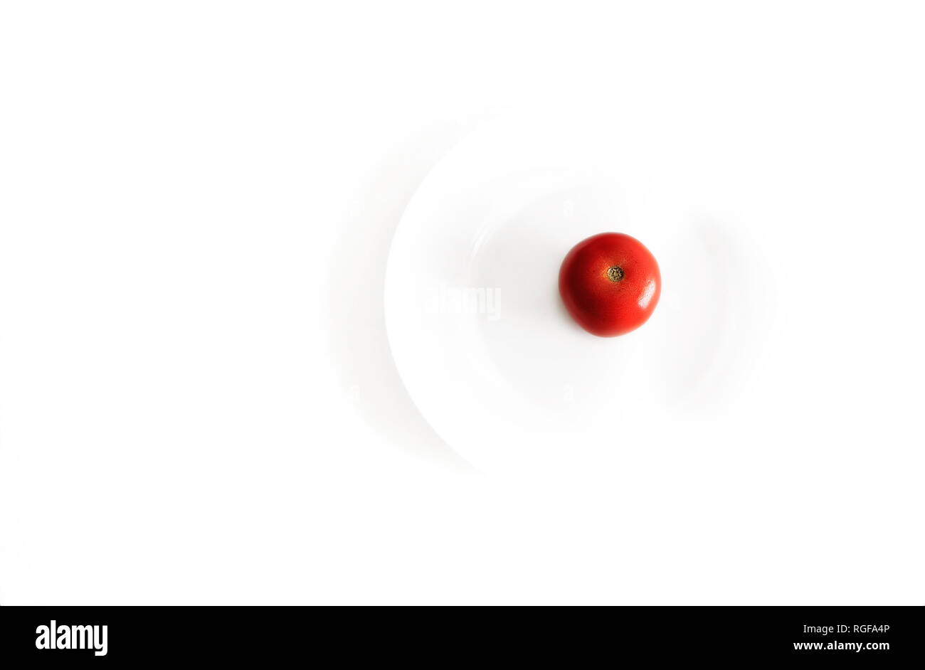 Red tomato on a white dish. Minimalist photography. - Stock Image