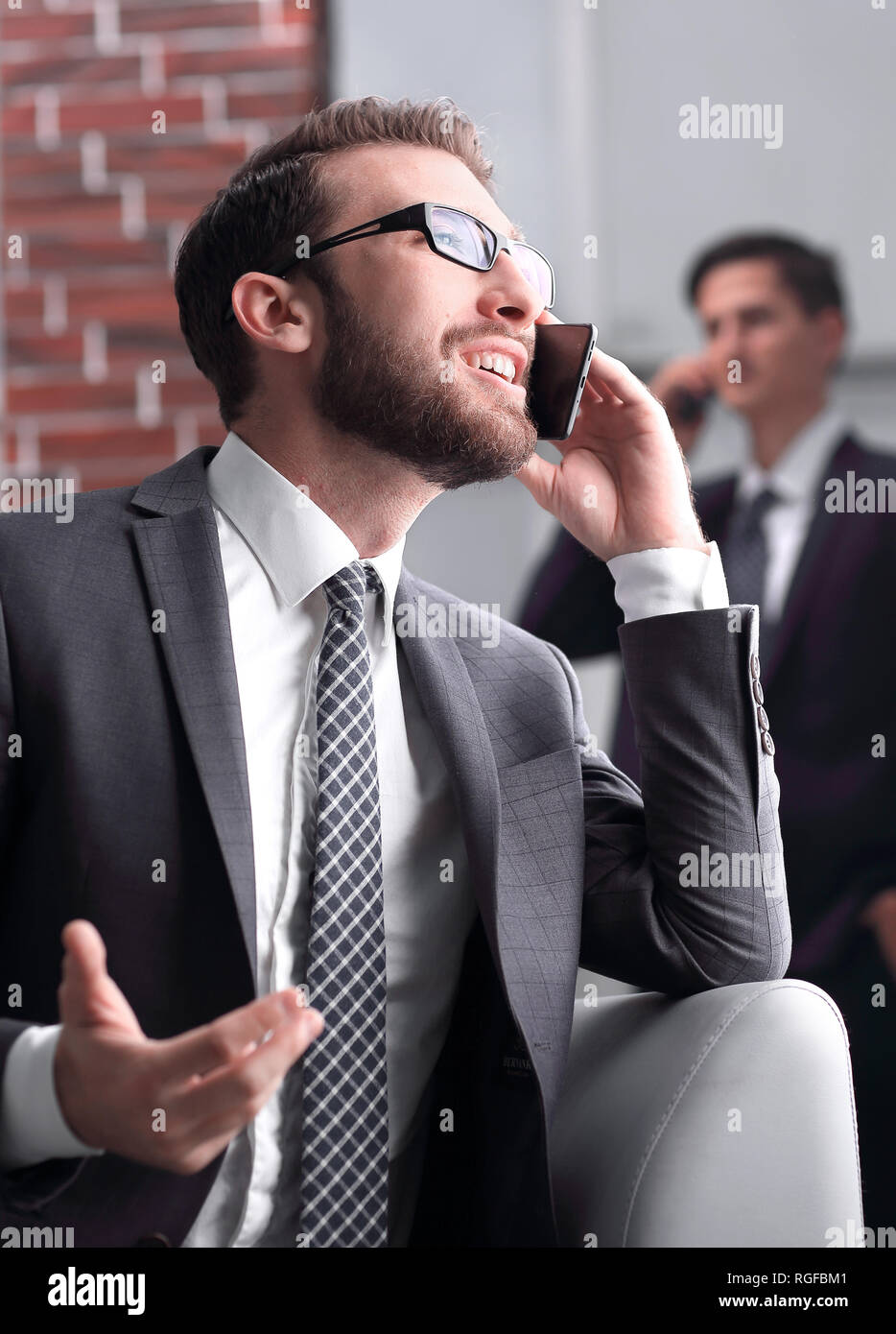 Handsome businessman speaking on mobile phone in office - Stock Image
