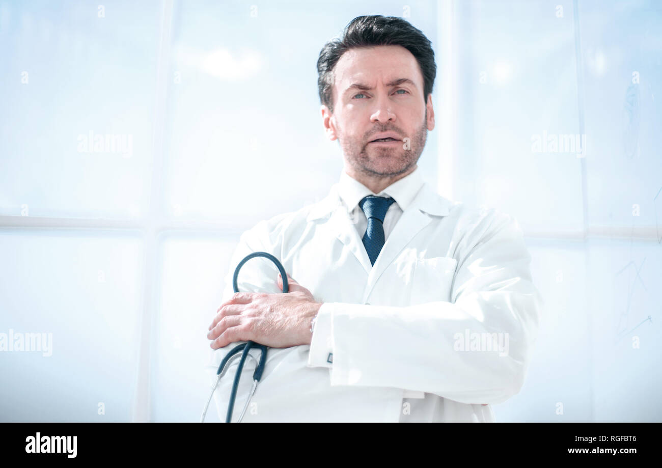 portrait of thoughtful doctor on blurred background - Stock Image