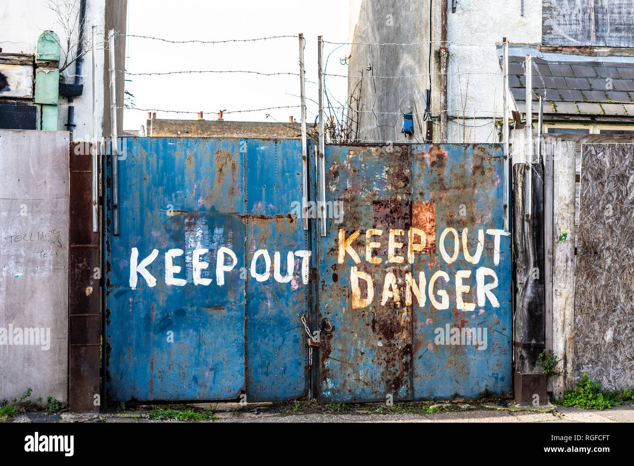 Old decaying building with warnings on gate to keep out. Danger keep out rough painted notice on rusting gates with barbed wire. Urban decay - Stock Image