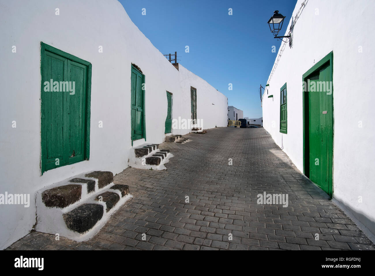 Alley with green doors in Teguise. Stock Photo