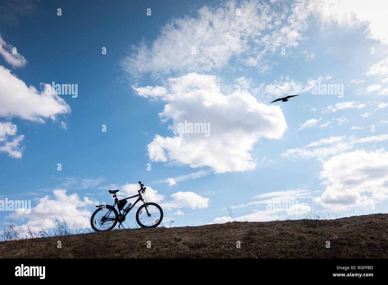 Bike silhouette in blue sky with clouds. symbol of independence and freedom with flying bird - Stock Image