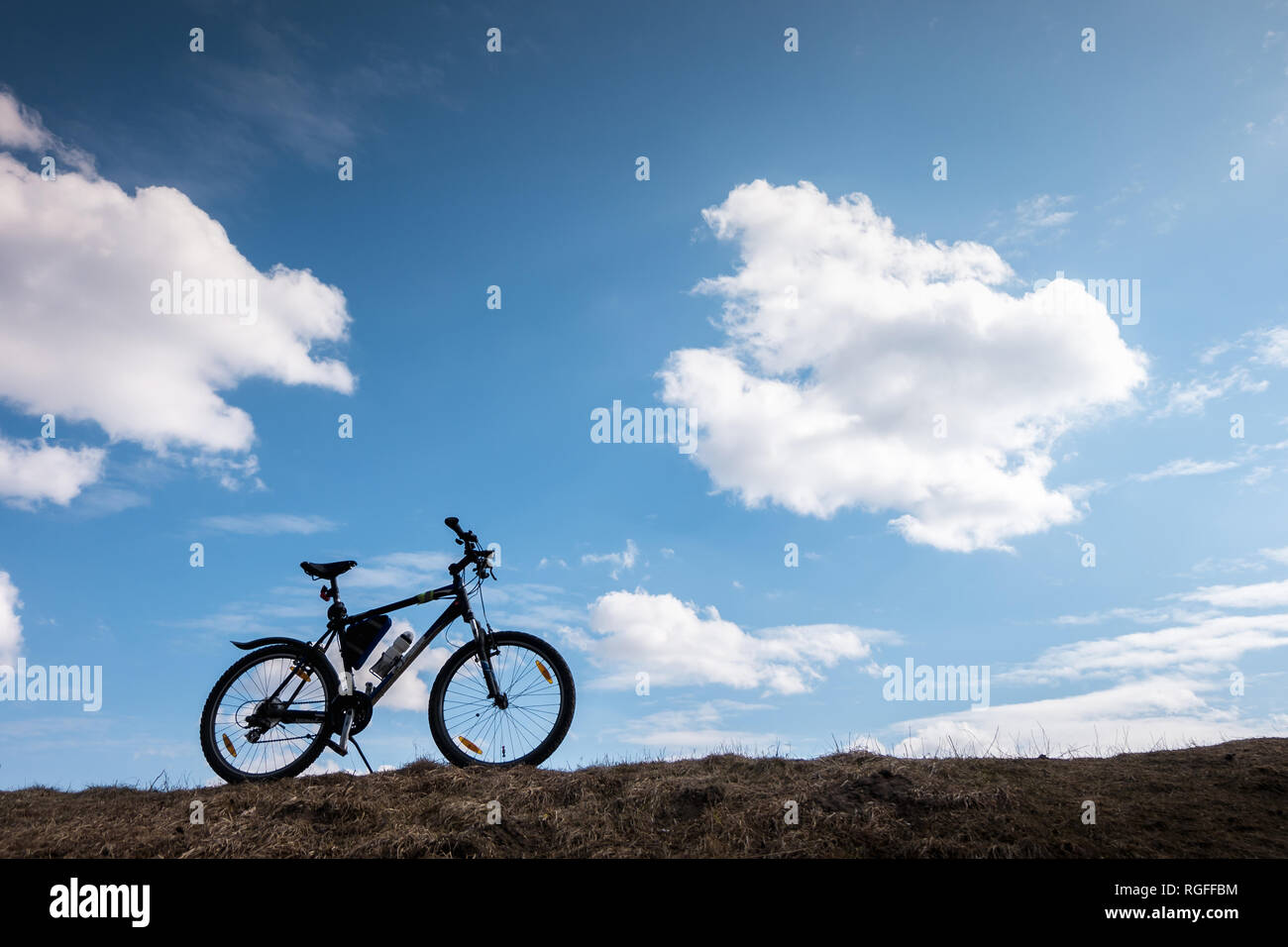 Bike silhouette in blue sky with clouds. symbol of independence and freedom - Stock Image