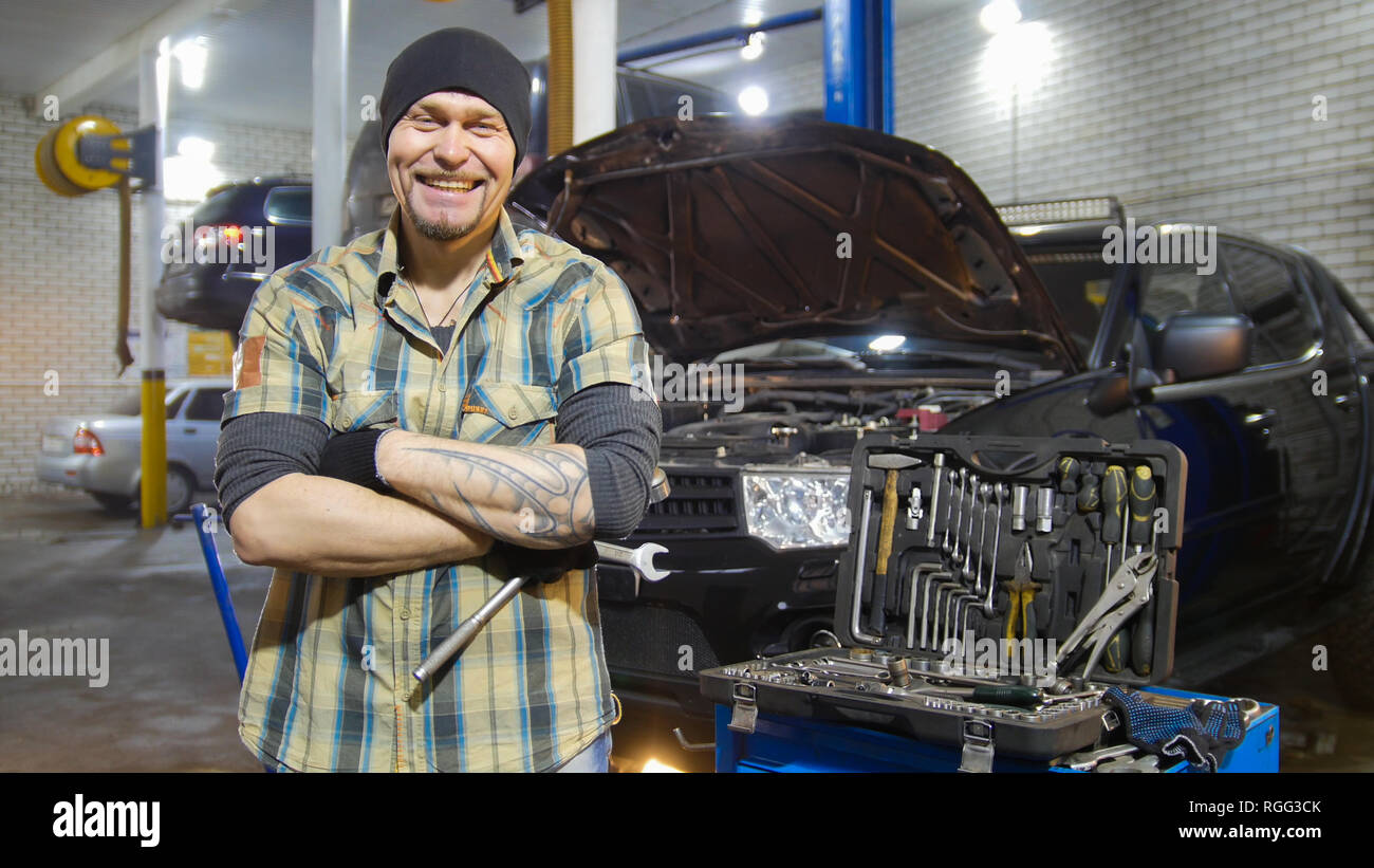 Car service. Brutal mechanic man standing by the car and grins - Stock Image