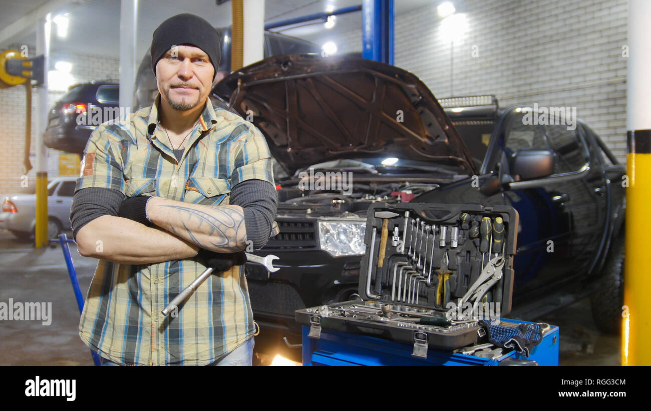 Car service. Brutal mechanic man standing by the car holding a wrench - Stock Image