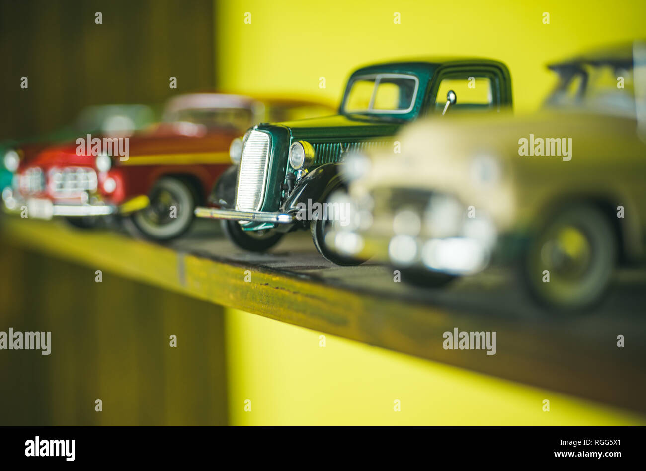 They look like real cars. Classic model vehicles or toy vehicles. Miniature collection of automobiles. Retro car models on shelf. Retro styled cars - Stock Image