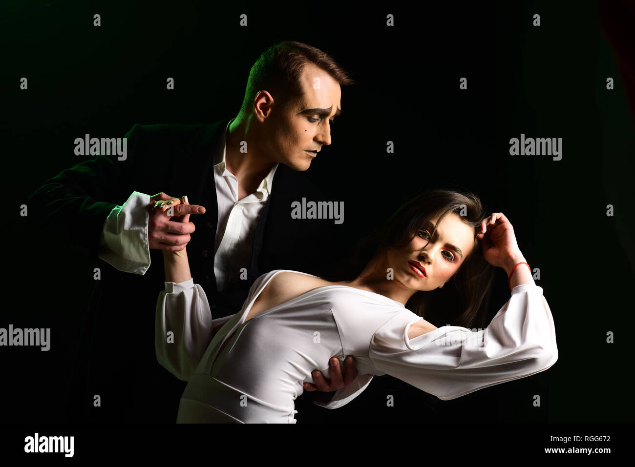 Making your heart flutter. Mime man and woman act in romantic scene. Couple of mime artists perform romance on stage. Theatre actors miming through - Stock Image
