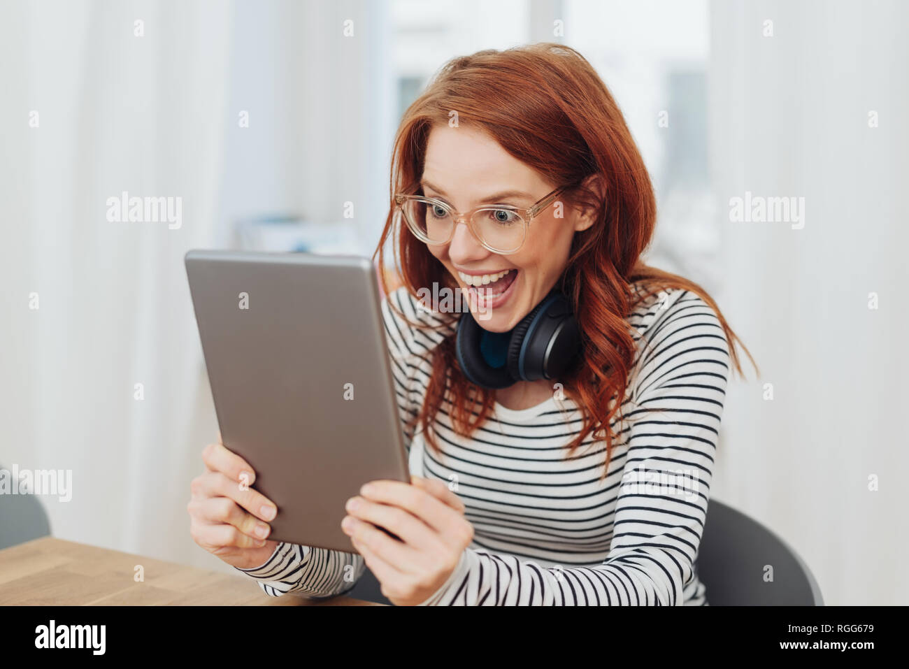 Excited young woman with a gleeful expression staring wide eyed at a handheld tablet computer with an elated smile - Stock Image