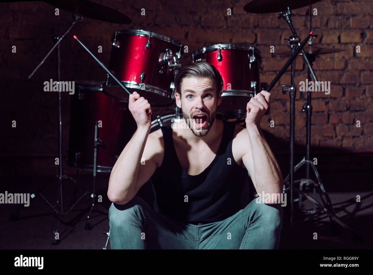 I beat things for a living. Excited man on stage at percussion instrument. Enjoying instrumental music. Man drummer with musical instrument. Rock - Stock Image