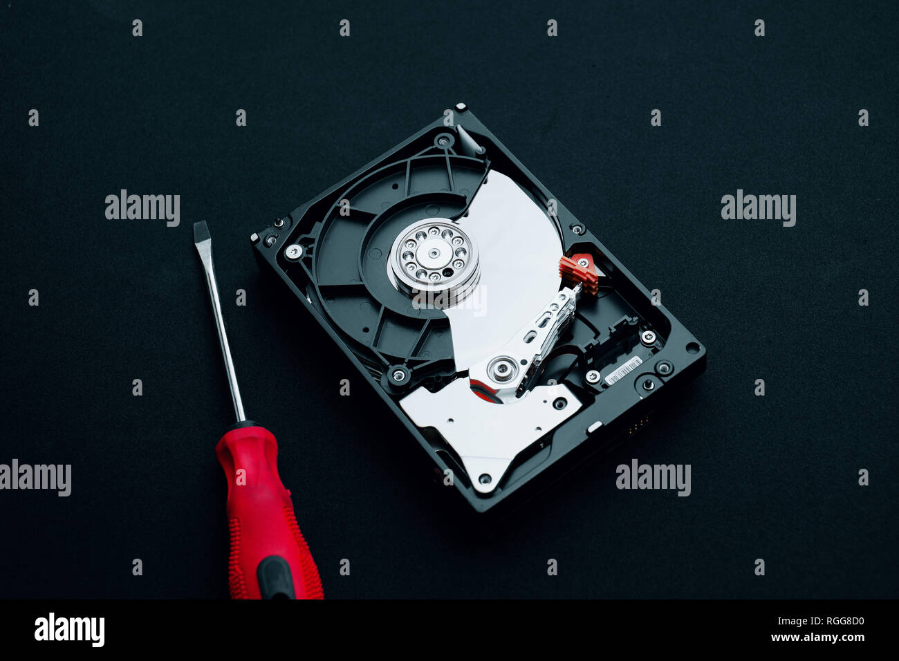 Computer hardware repair and inspection concepts, Disassembled hard disk drive with a screwdriver. - Stock Image