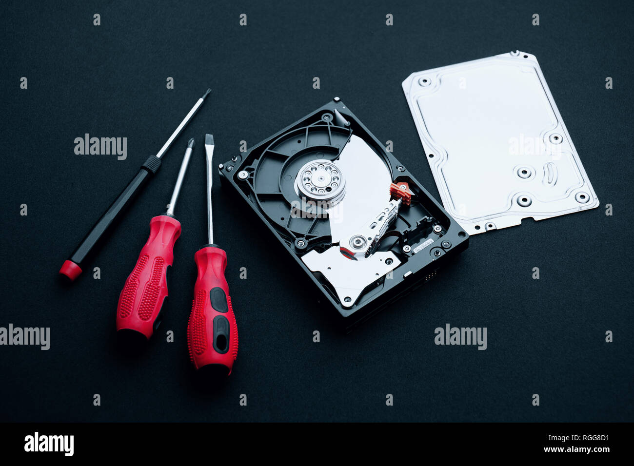 Data storage hard disk drive uncovered with assembly case cover part and screwdrivers, Computer hardware repair concepts. - Stock Image