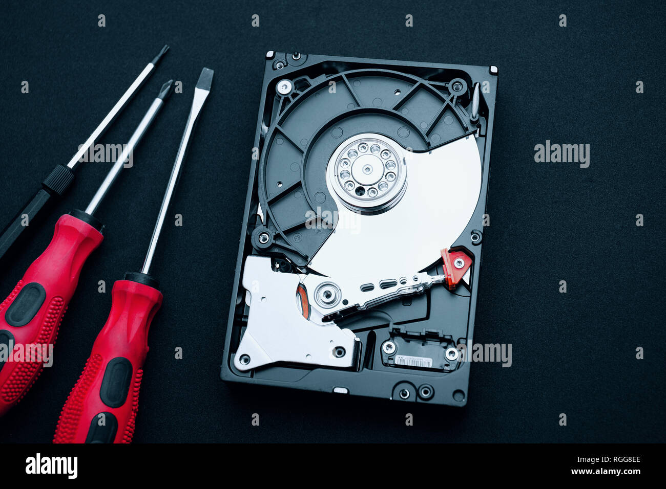 Top view of uncovered hard drive and screwdrivers on the desk. Hardware assembly inside showing magnetic platters discs and actuator read/write arm. - Stock Image