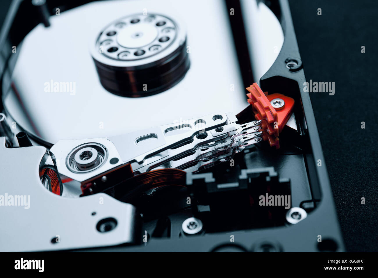 Closeup inside the assembly of hard disk drive actuator arm with read/write head and multi-layer magnetic platters discs. - Stock Image