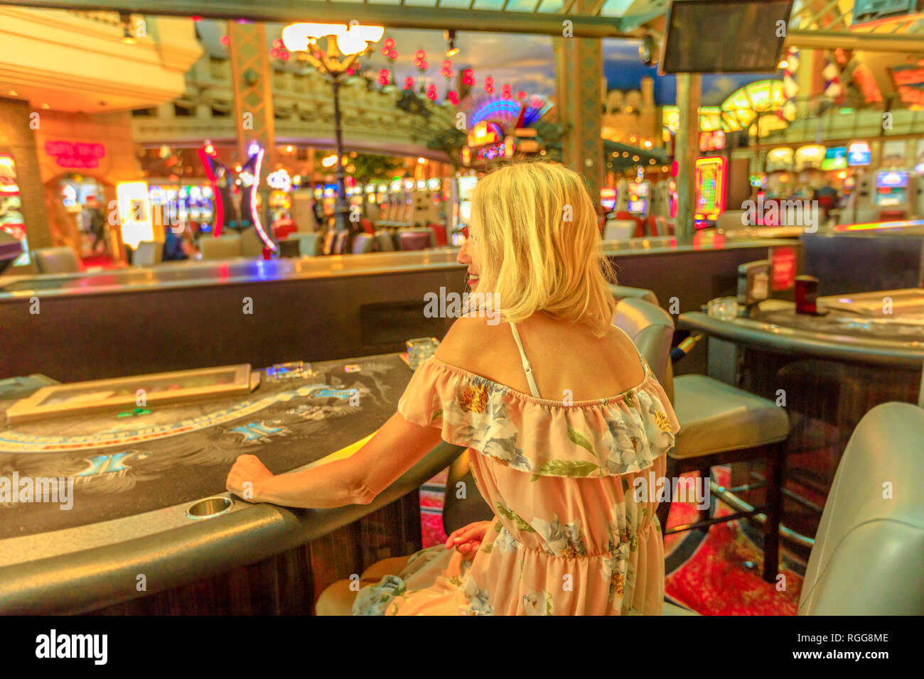 Back side of caucasian blonde woman gambling in casino with bright lights. Lifestyle girl waiting to play at blackjack in Las Vegas, Nevada, United - Stock Image