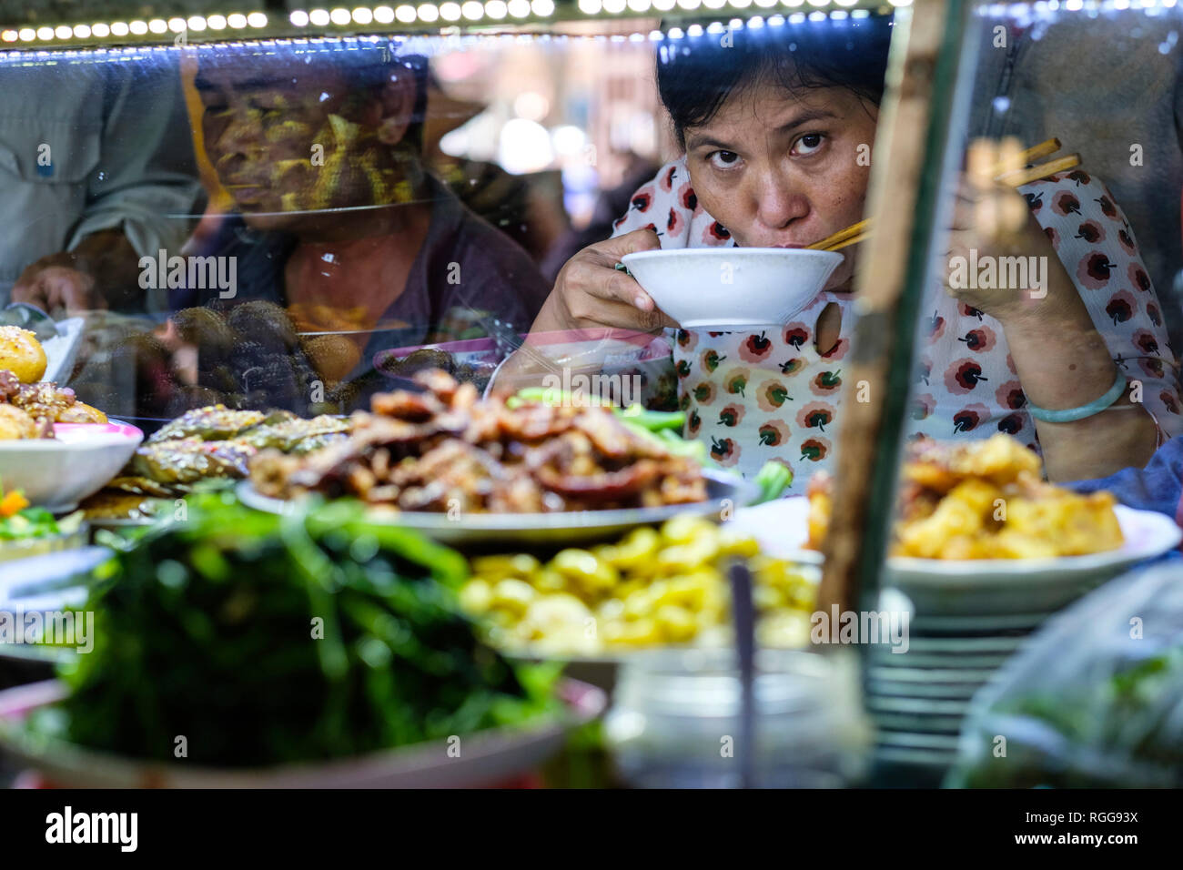 Woman looking at camera while eating street food with chopsticks at a market in Hoi An, Vietnam, Asia - Stock Image