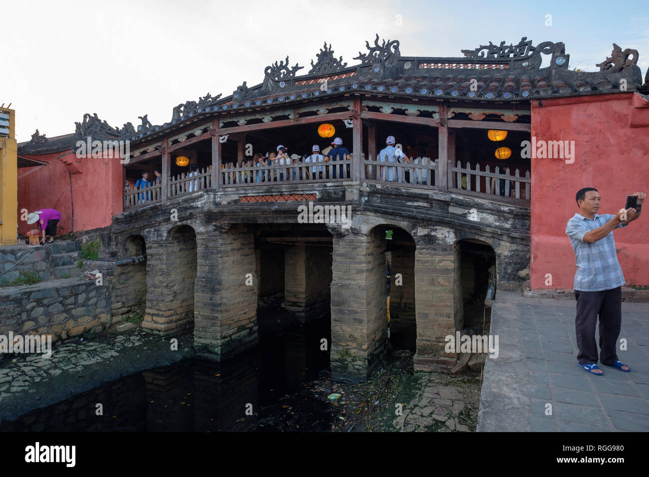 Tourist taking a selfie with his smartphone in front of the Japanese Covered Bridge aka Cau Chua Pagoda in Hoi An, Vietnam Stock Photo
