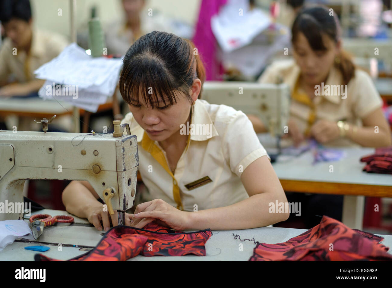 Women with sewing machines working at a garment factory in Vietnam, Asia - Stock Image