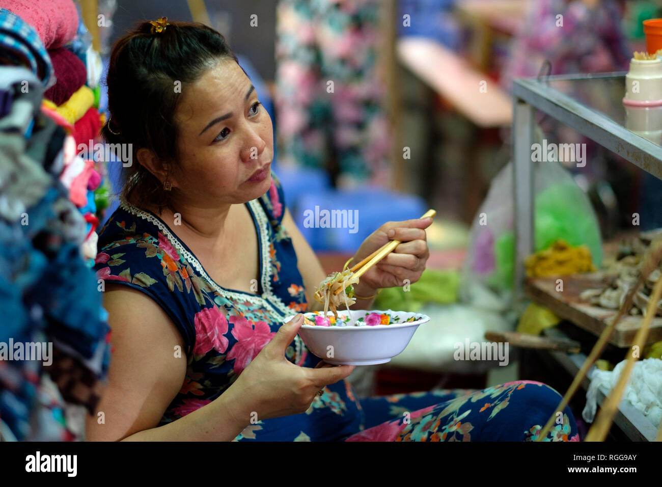 Woman eating street food with chopsticks at Dong Ba market in Hue, Vietnam, Asia - Stock Image