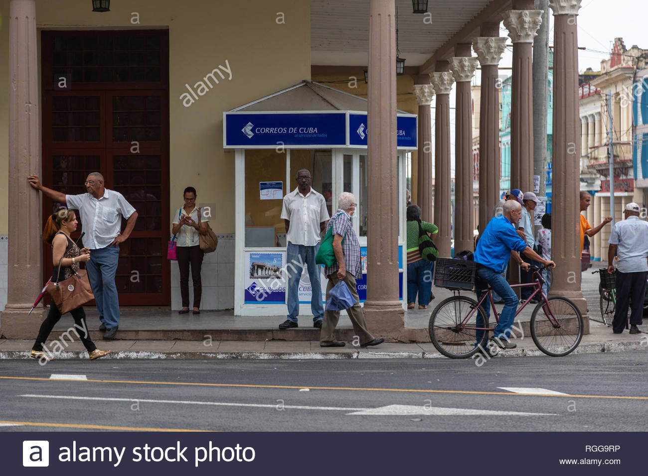 Street scene somewhere in Cuba of people hanging around or on their way. - Stock Image