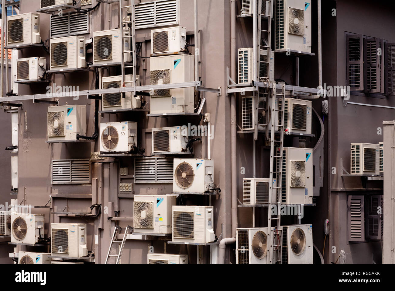 Masses of air conditioning units on the side of a block of flats, Singapore. - Stock Image
