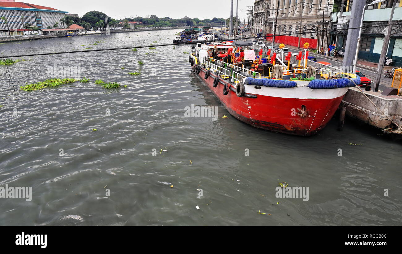 Red-white painted anchor-aweigh ship moored at the dock on the north bank of the Pasig river as seen from the Willian A.Jones Memorial Bridge linking  - Stock Image
