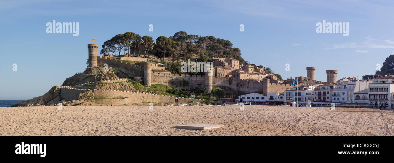 Fortress of Tossa de Mar with the beach and new town: The massive stone defensive wall and towers of this landmark rise from the sandy beach along the Catalonian coast. Boats are pulled up on the beach below and the new town clusters along the beach. - Stock Image