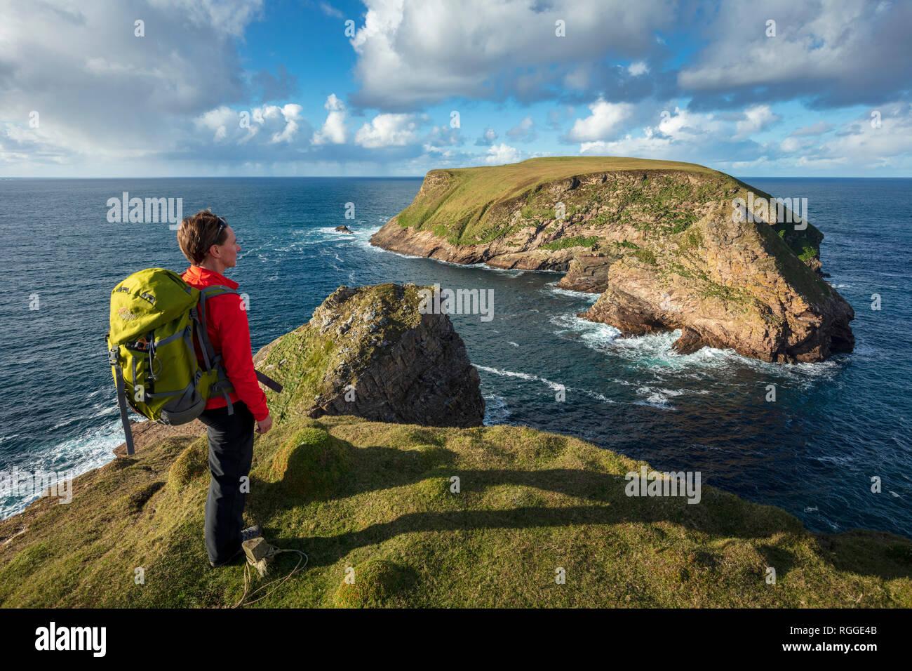 Coastal walker looking towards Kid Island, on the Children of Lir coast walk. Carrowteige, County Mayo, Ireland. - Stock Image