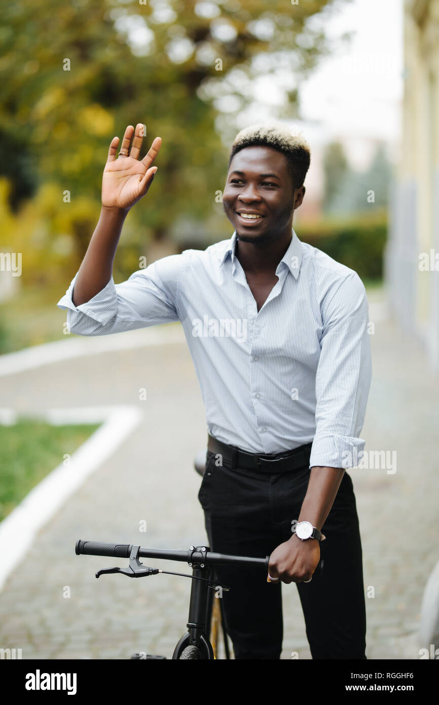 Young african man in suit greeting someone on the street while walking with bicycle outdoors - Stock Image