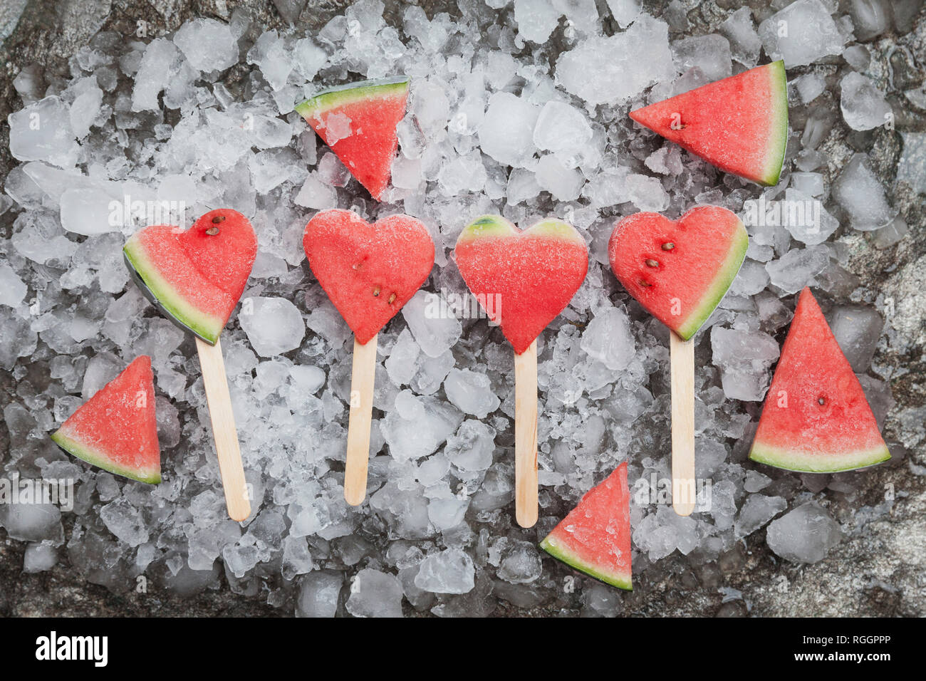 Watermelon heart ice lollies on crashed ice - Stock Image