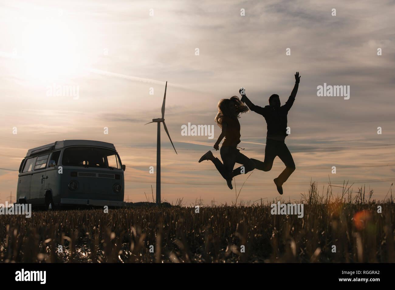 Exuberant couple jumping at camper van in rural landscape at dusk Stock Photo