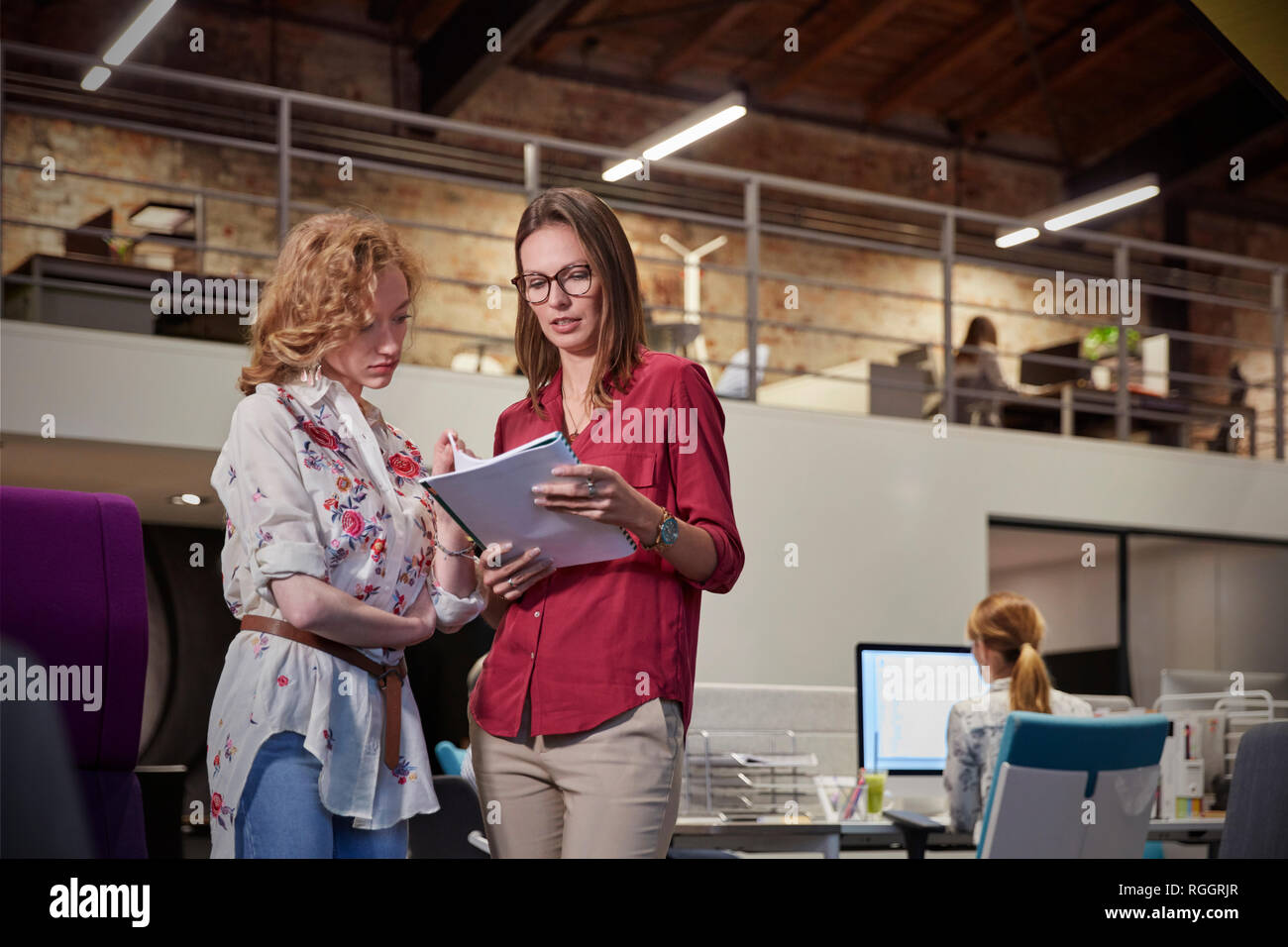 Woman explaining younger collague a project - Stock Image