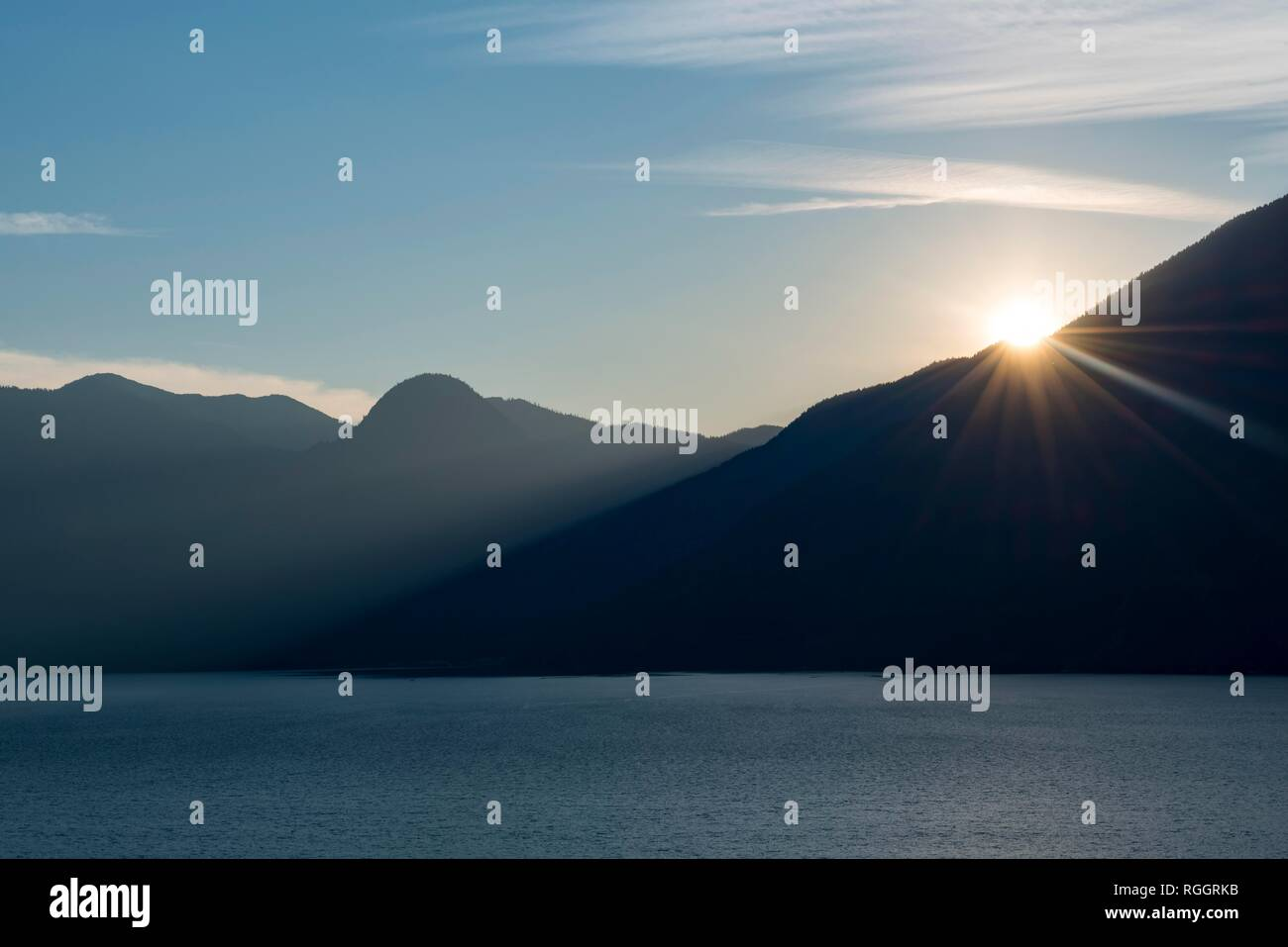 Evening sun shines over mountain silhouette, Howe Sound, Squamish, British Columbia, Canada Stock Photo