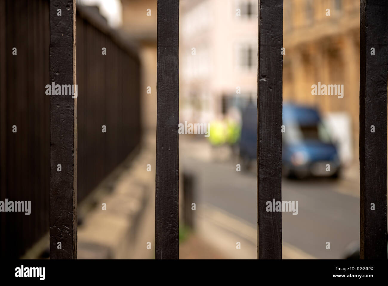 Metal security bars close up closeup close-up.. Out of focus policemen in hi vis vests and blue van. Criminal crime concept. - Stock Image