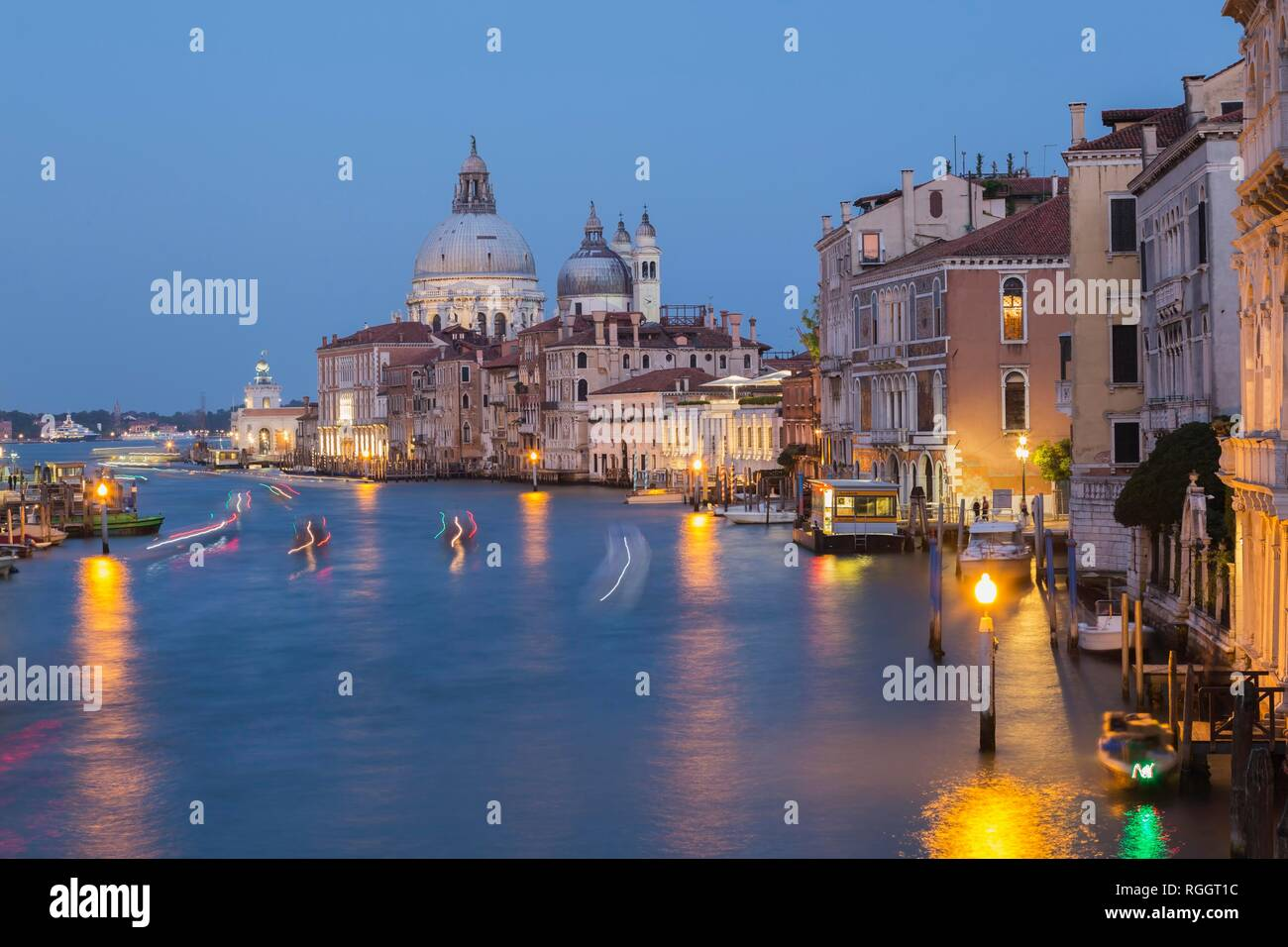 Grand Canal with light trails from water taxis, vaporettos in movement plus Renaissance architectural style palace buildings and - Stock Image