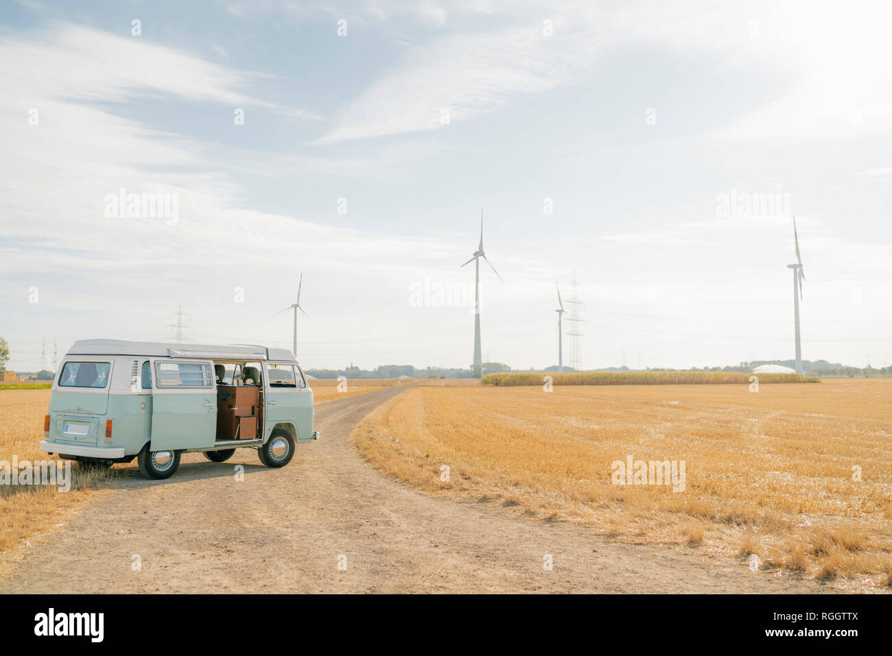 Camper van parked on dirt track in rural landscape with wind turbines Stock Photo