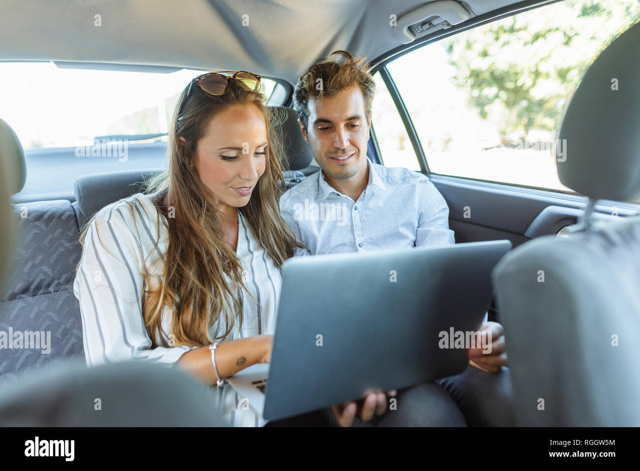 Couple using laptop on back seat of a car - Stock Image