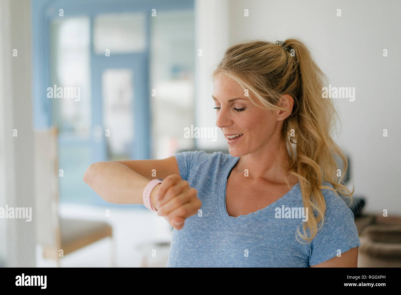 Smiling Blond Woman Checking The Time