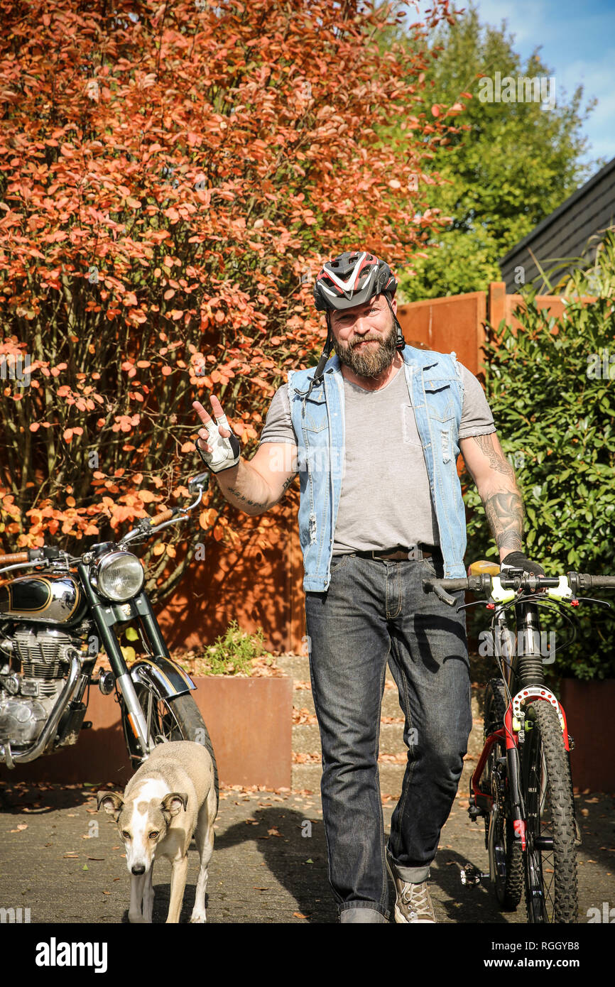 Portrait of man switching from motorbike to bicycle Stock Photo
