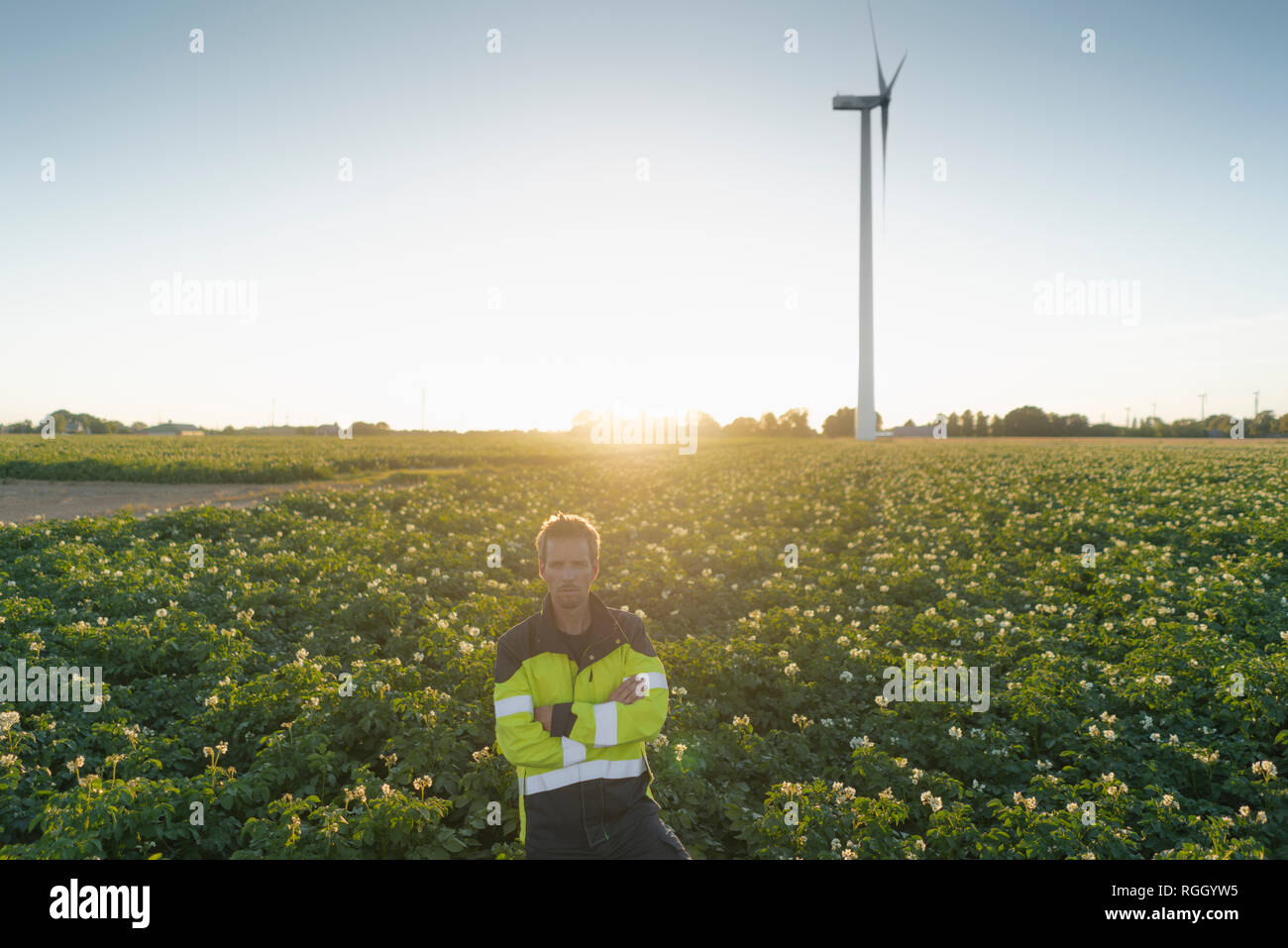 Engineer standing in a field at a wind turbine Stock Photo