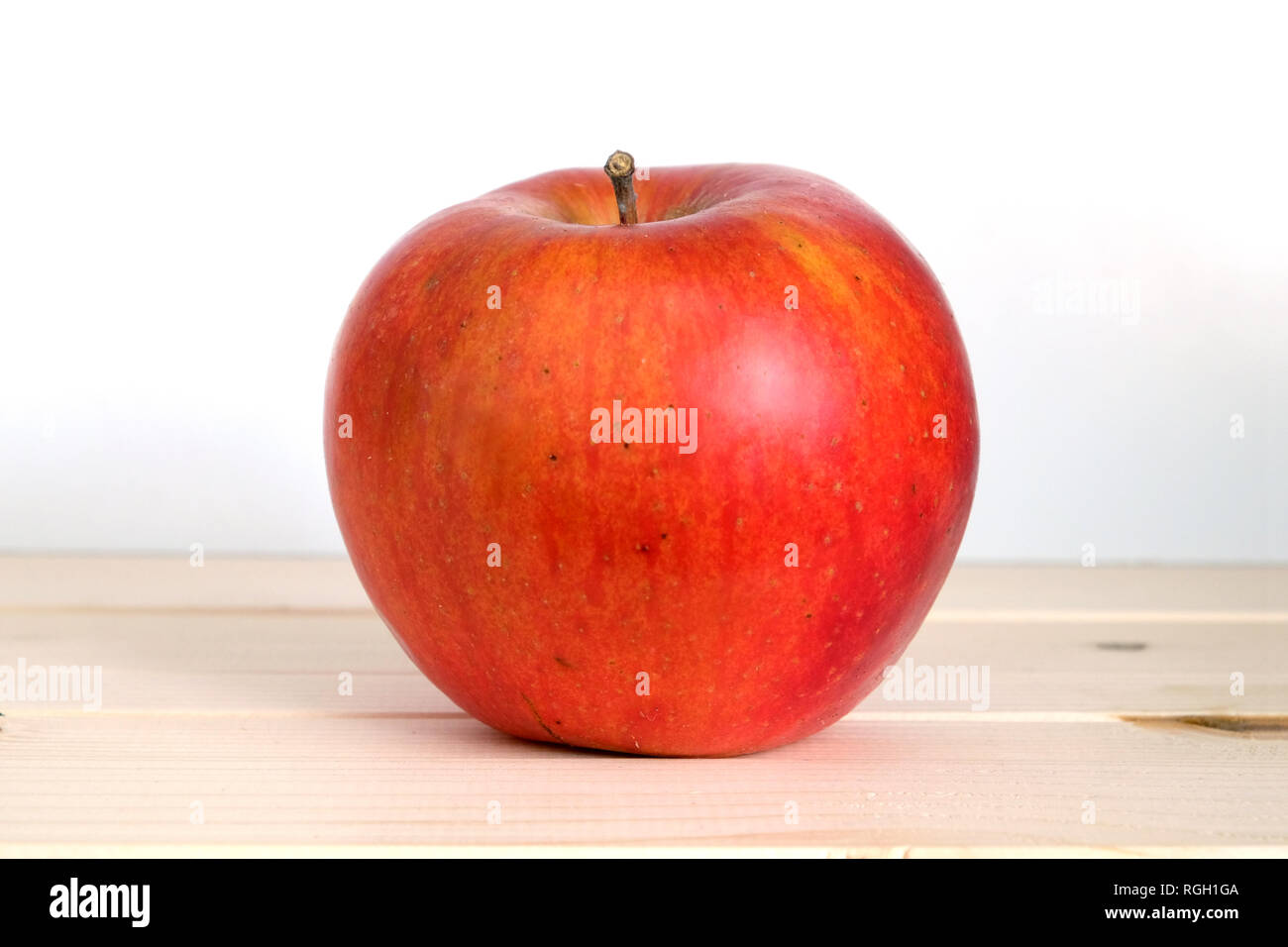 Big ripe red apple in beige wooden shelf on white background front view closeup - Stock Image