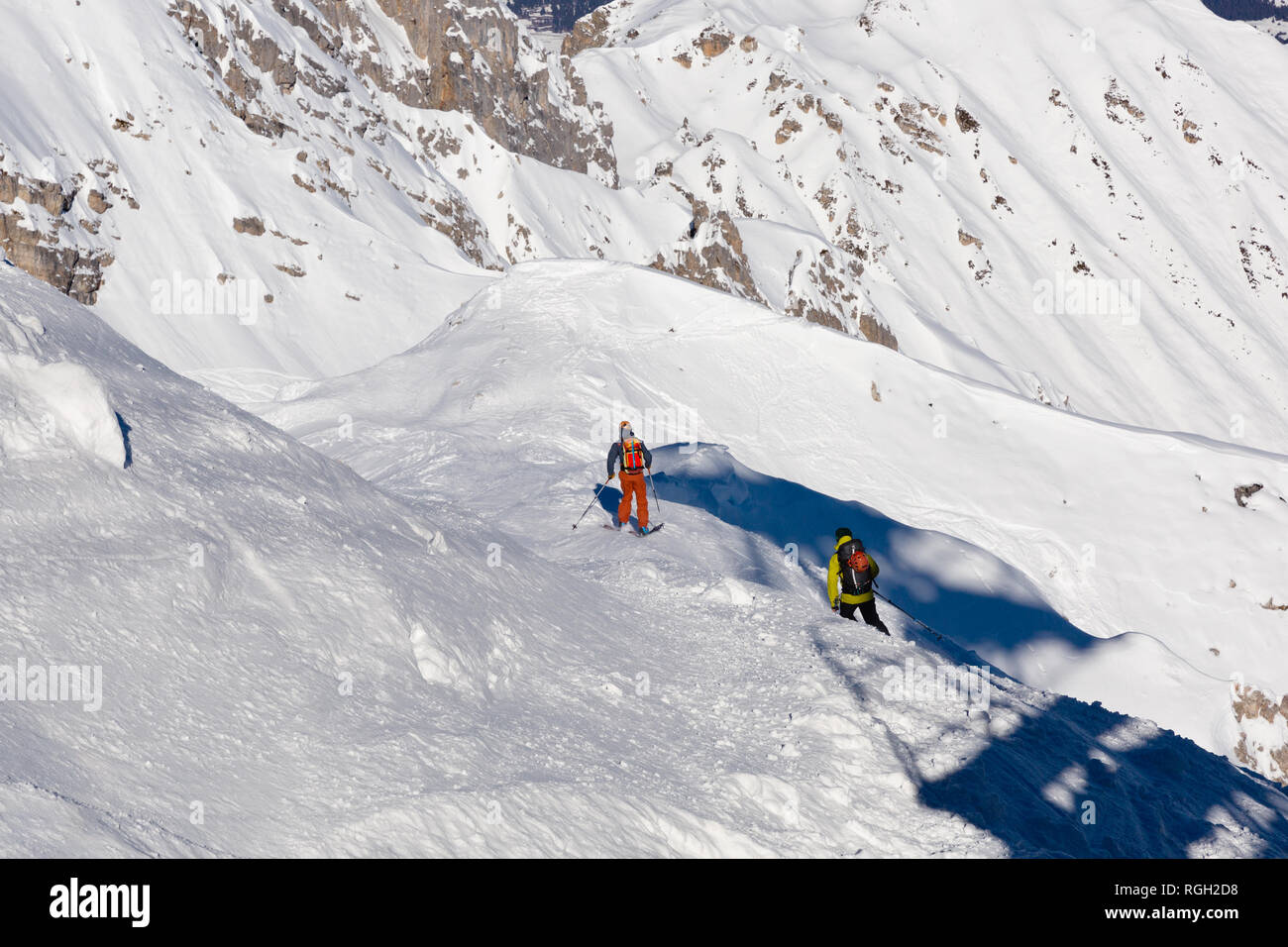 Skiing, Skier, Free ride in fresh powder snow - Man with skis climbs to the top - Stock Image