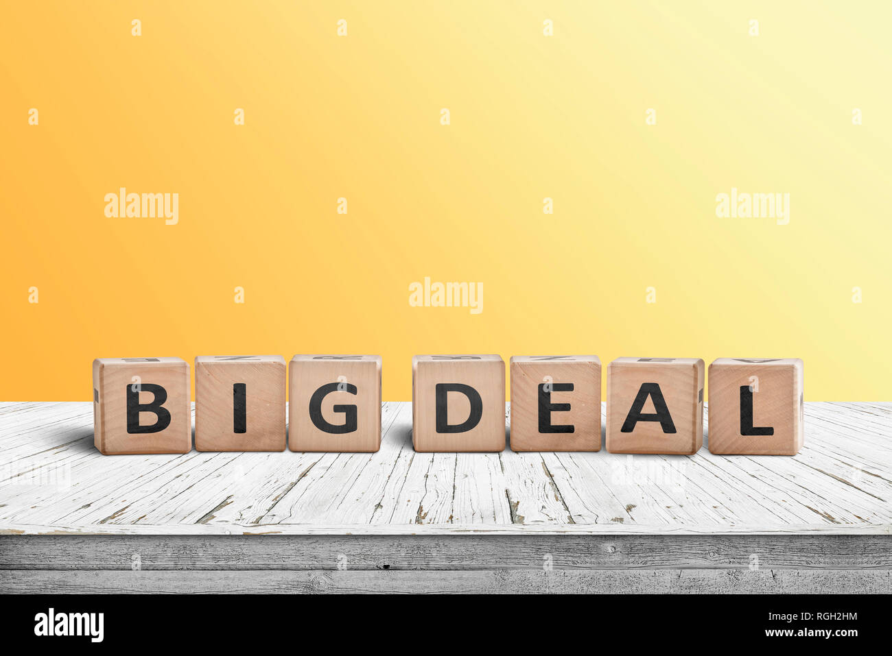 dd51d51eb84 Big deal sign made of wooden cubes on a desk with a yellow wall in the  background