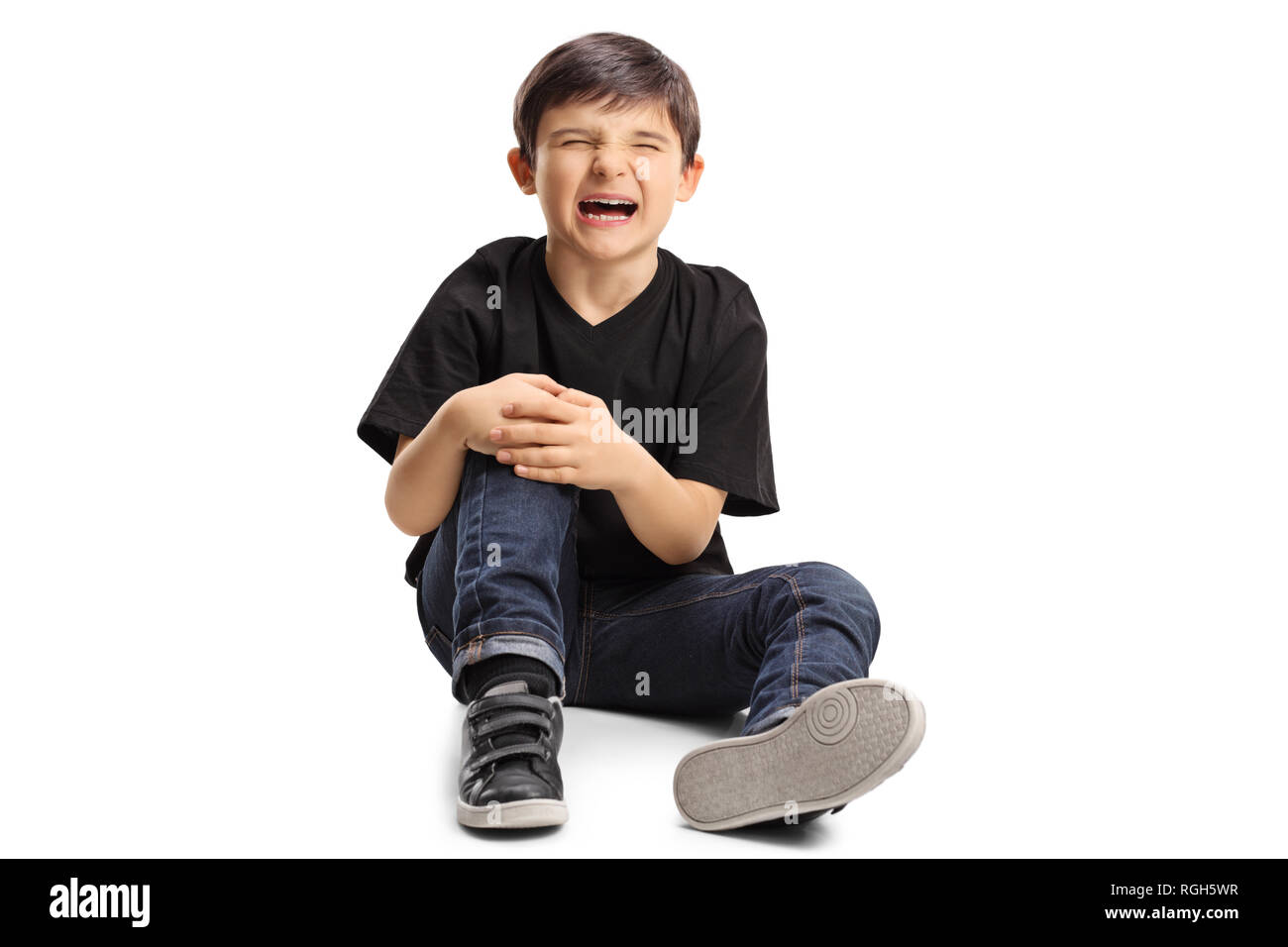 A boy sitting on the floor in pain, holding his knee and crying isolated on white background - Stock Image