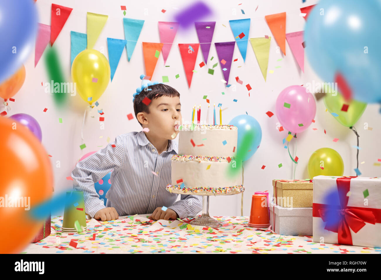 Boy blowing candles from a birthday cake at a party with baloons and presents around him - Stock Image