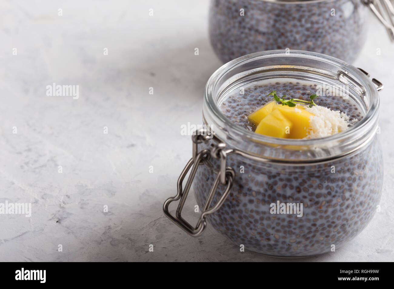 Mango chia dessert with plant milk in glass jar, vegan  snack or dessert on light grey background, healthy eating Stock Photo