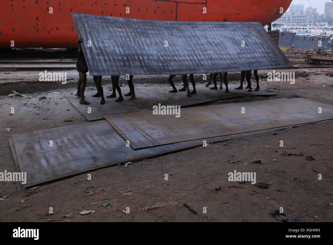 Workers carry a heavy piece of metal sheet at a Shipyard in Dhaka, Bangladesh on January 29, 2019. Dozens dockyards occupying 30.96 acres of the Buriganga foreshore have been in operation for the last 50 years. It is mostly utilized for fixing and repairing old ships, build in new ships. Labors work in the dockyard without helmets, face mask, or safety shoes as their ages from 8 to 80 years old. Nearly 15,000 labors including children work in this yard from dawn to dusk as they get paid about $5 each day. © Rehman Asad / Alamy Stock Photo Stock Photo