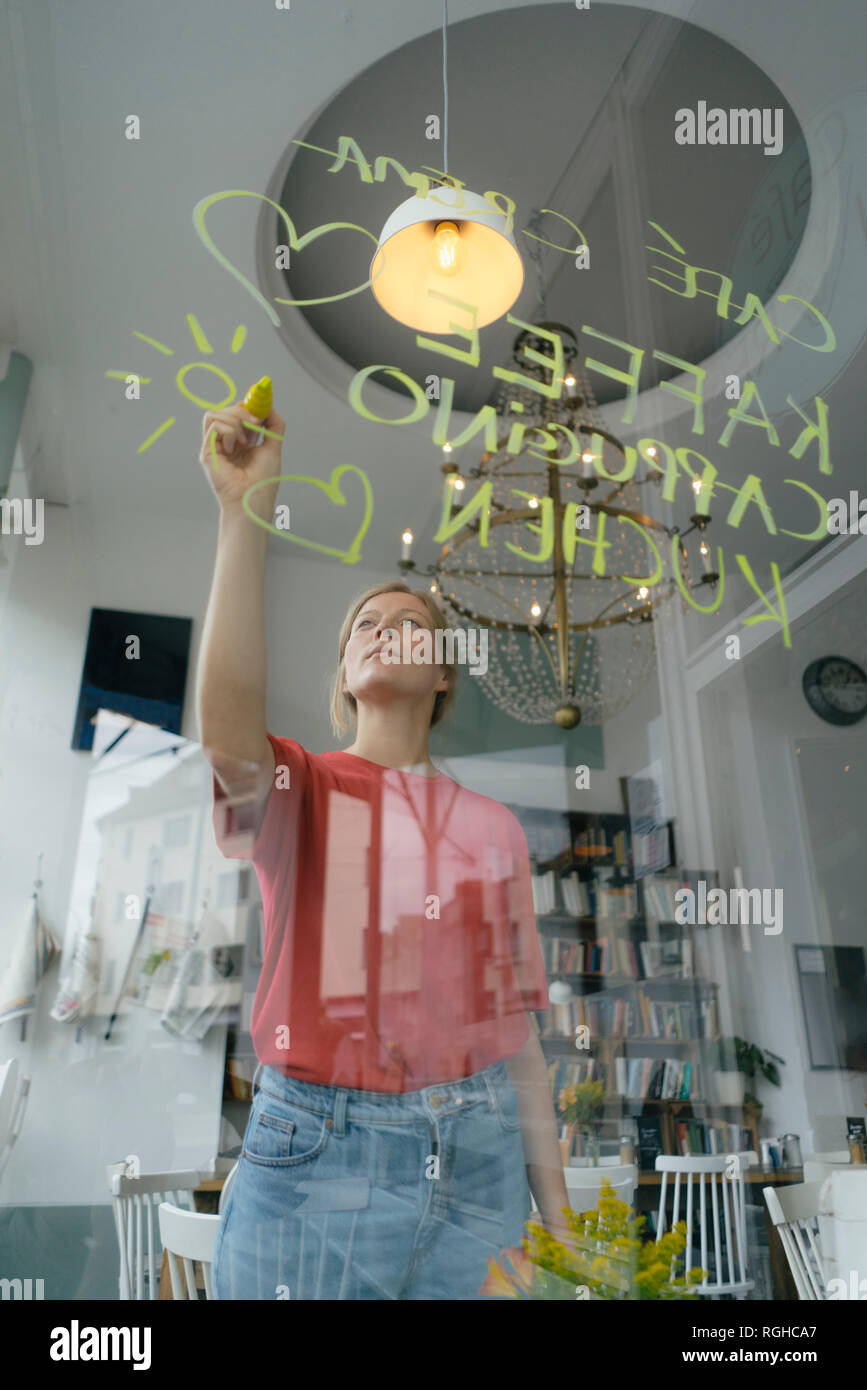 Young woman writing offer on windowpane in a cafe - Stock Image